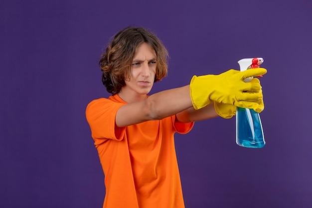 Młody człowiek w pomarańczowej koszulce w gumowych rękawiczkach trzymający spray do czyszczenia, używając jako pistoletu, patrząc na bok z poważnym, pewnym siebie wyrazem twarzy, stojąc na fioletowym tle