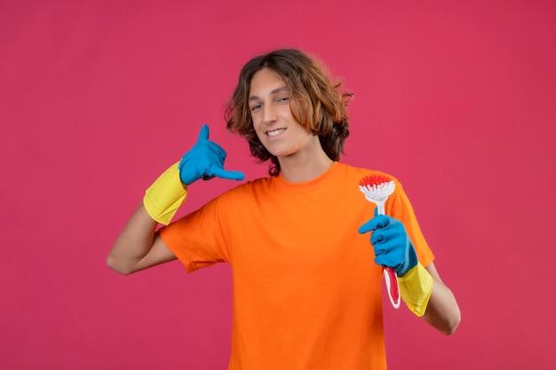 Młody człowiek w pomarańczowej koszulce w gumowych rękawiczkach trzymający szczotkę do szorowania patrząc na kamerę z pewnym siebie uśmiechem, wykonujący gest zadzwoń do mnie stojący na różowym tle