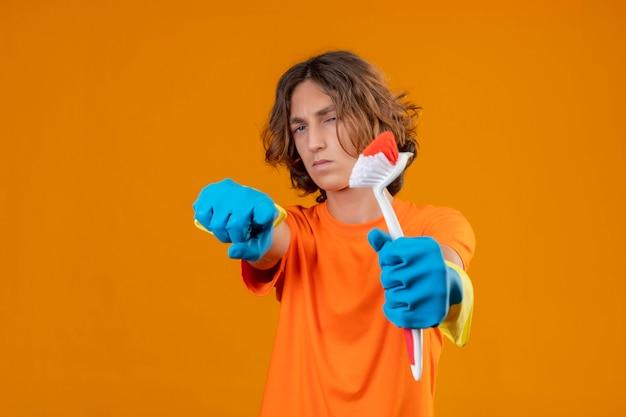 Młody człowiek w pomarańczowej koszulce w gumowych rękawiczkach trzymający szczotkę do szorowania wskazujący na aparat z podejrzanym wyrazem twarzy stojącej na żółtym tle