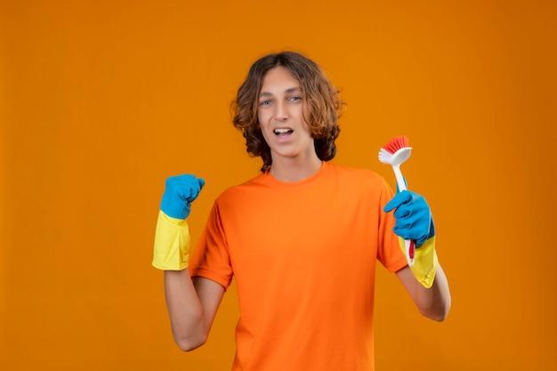 Młody człowiek w pomarańczowej koszulce w gumowych rękawiczkach trzymający szczotkę do szorowania zaciskającą pięść, ciesząc się swoim sukcesem i zwycięstwem wyszedł i szczęśliwy stojąc na żółtym tle