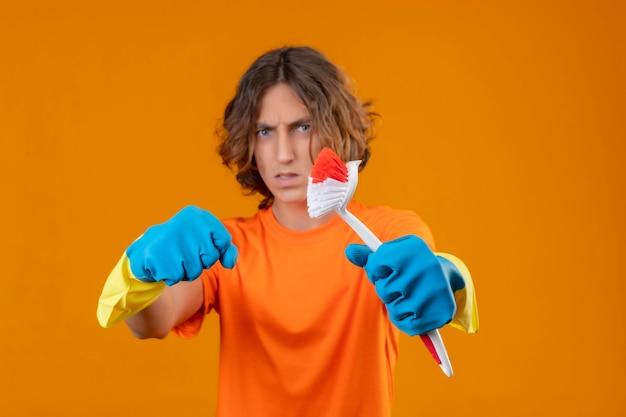 Młody człowiek w pomarańczowej koszulce w gumowych rękawiczkach trzymający szczotkę do szorowania zaciskający pięść do aparatu z gniewnym wyrazem twarzy stojącej na żółtym tle