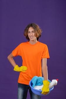 Młody człowiek w pomarańczowej koszulce w gumowych rękawiczkach trzymający umywalkę z narzędziami do czyszczenia patrząc na kamerę z pewnym uśmiechem na twarzy stojącej na fioletowym tle