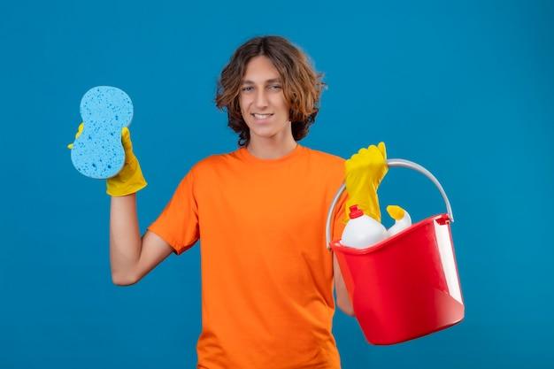 Młody człowiek w pomarańczowej koszulce w gumowych rękawiczkach trzymający wiadro z narzędziami do czyszczenia i gąbką patrząc na kamerę uśmiechnięty wesoło szczęśliwy i pozytywny stojąc na niebieskim tle