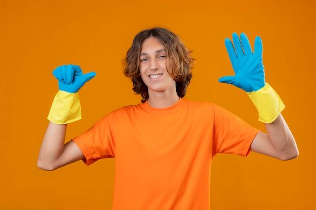 Młody człowiek w pomarańczowej koszulce w gumowych rękawiczkach, uśmiechając się z radosną twarzą pokazując palcami numer sześć i wskazując w górę na żółtym tle