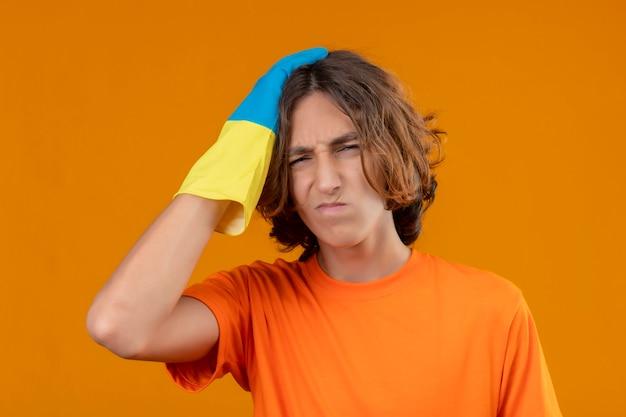Młody człowiek w pomarańczowej koszulce w gumowych rękawiczkach z ręką na głowie za pomyłkę pamięta błąd zapomniał o złej koncepcji pamięci stojącej na żółtym tle