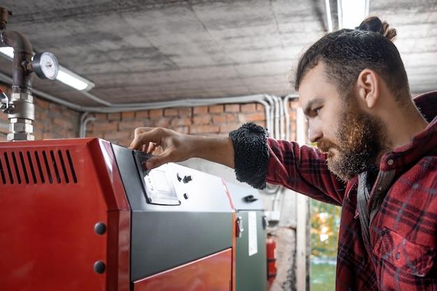 Młody człowiek w pomieszczeniu z kotłem na paliwo stałe, pracujący na biopaliwo, oszczędne ogrzewanie.