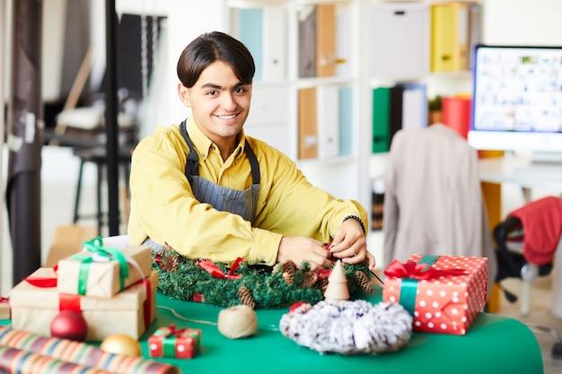 Młody człowiek w pracy, robiąc wieniec i pakując prezenty
