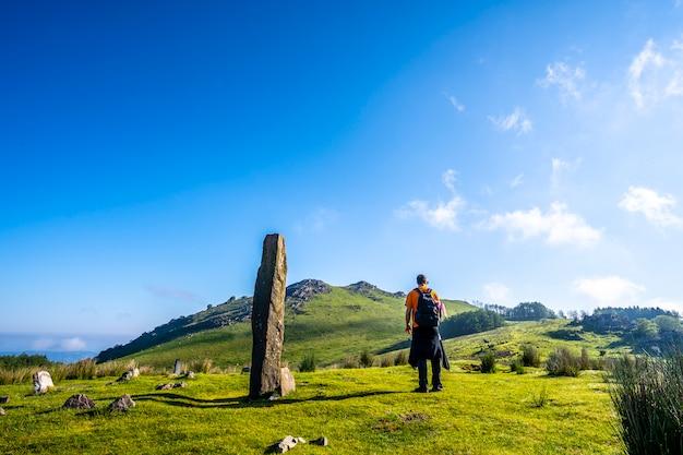 Młody człowiek w prehistorycznym dolmenie na szczycie monte adarra w urniecie, niedaleko san sebastian. gipuzkoa, kraj basków