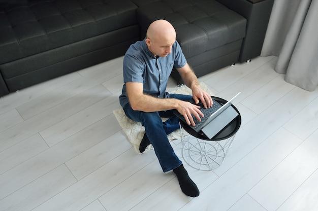Młody człowiek w przypadkowych ubraniach siedzi na podłoga i pracuje na jego laptopie w domu.