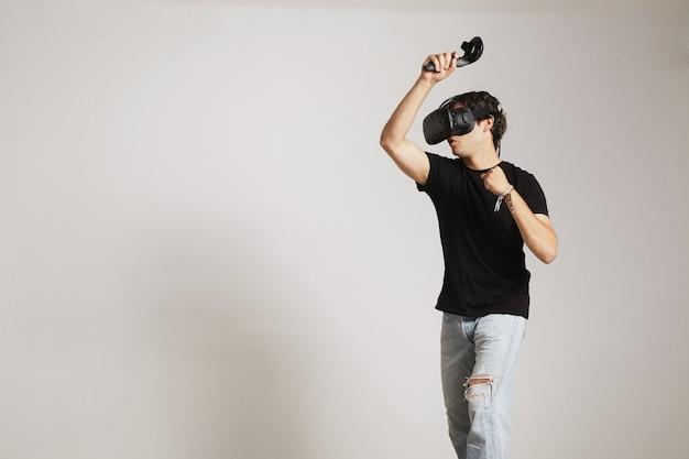 Młody człowiek w pustej czarnej koszulce gry w golfa lub tenisa w zestaw słuchawkowy vr uderzając coś na białym tle