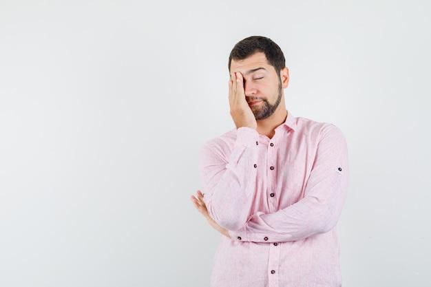 Młody człowiek w różowej koszuli, trzymając rękę na twarzy i patrząc śpiący