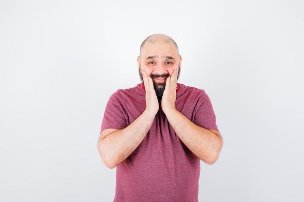 Młody człowiek w różowym t-shirt, kładąc ręce w pobliżu ust i patrząc optymistycznie, widok z przodu.
