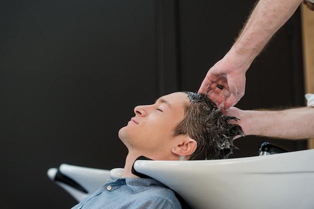Młody człowiek w salonie fryzjerskim, myje włosy