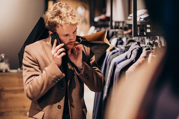 Młody człowiek w sklepie z odzieżą męską rozmawia przez telefon