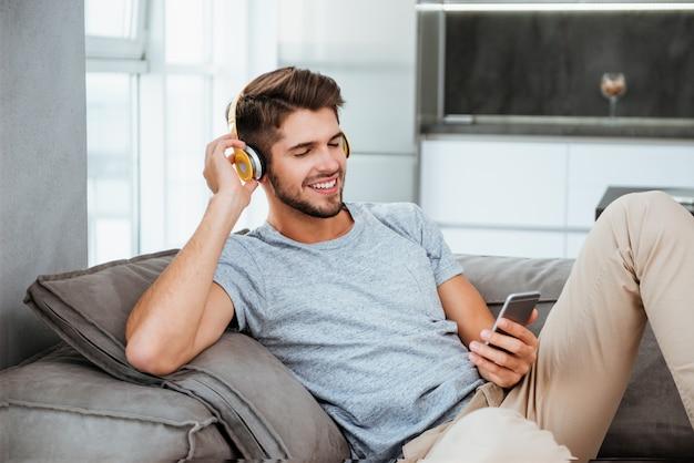 Młody człowiek w słuchawkach, słuchanie muzyki, leżąc na kanapie. patrząc na telefon i rozmawiając.