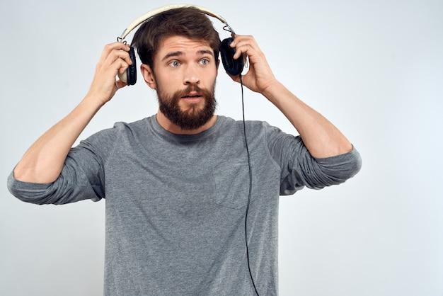 Młody człowiek w słuchawkach, słuchanie muzyki na białym tle
