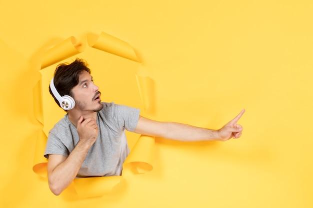 Młody człowiek w słuchawkach ze zszokowaną twarzą na rozdartym żółtym tle dźwięk ultradźwięków dźwiękowych
