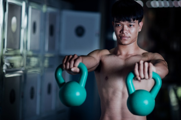 Młody człowiek w sportowej klasy ćwiczeń w siłowni