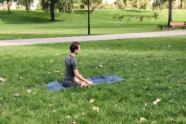 Młody człowiek w sportowej robi joga w parku. ćwicz asany na świeżym powietrzu. ćwiczenia na zielonej trawie z matą do jogi. mężczyzna siedzący w pozycji lotosu, spokój i medytacja. fitness i zdrowy styl życia