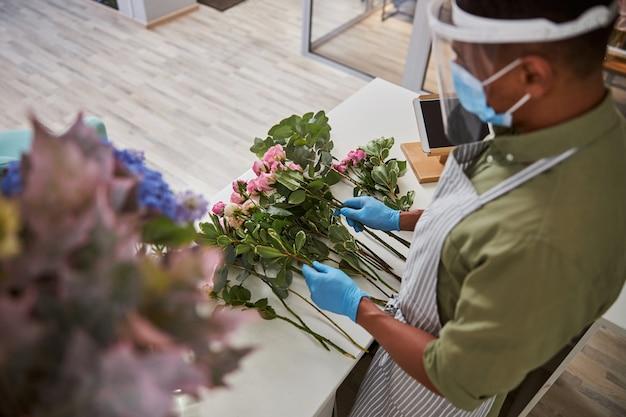 Młody człowiek w sterylnej masce i szkle ochronnym robi bukiety różowych róż w sklepie