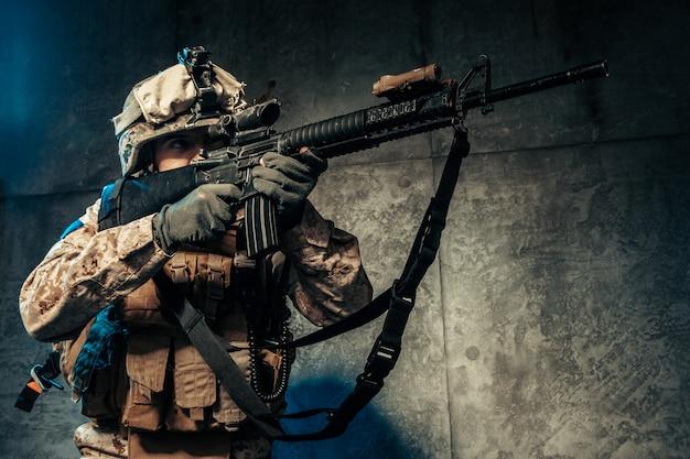 Młody człowiek w stroju wojskowym najemnika żołnierza w czasach współczesnych na ciemnym tle w studio
