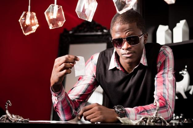 Młody człowiek w stylowej odzieży casual i okulary przeciwsłoneczne, siedzi przy stole i oferuje leki w małym opakowaniu