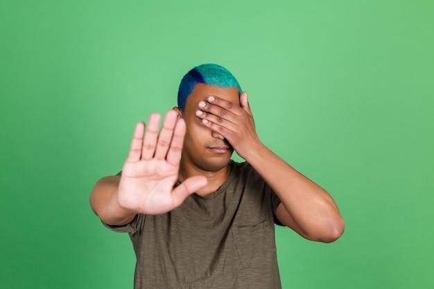 Młody człowiek w swobodnym stylu na zielonej ścianie zakrywa oczy rękami pokazując gest zatrzymania