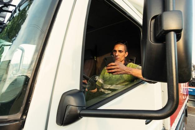 Młody człowiek w swojej ciężarówce w kabinie z ubraniami bezpieczeństwa za pomocą smartfona
