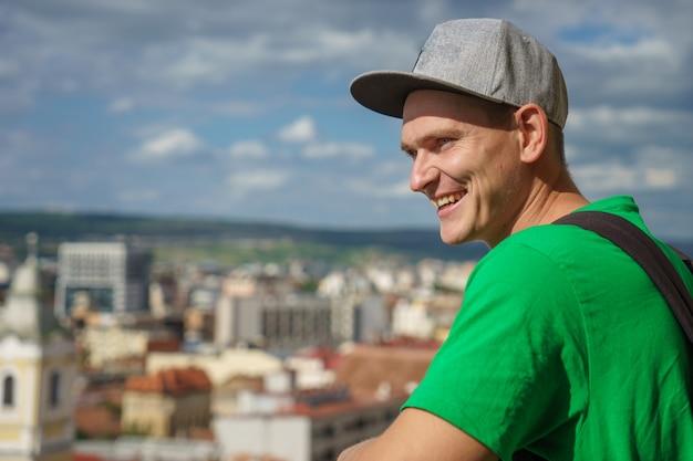Młody człowiek w szarej czapce z daszkiem i zielonej koszulce na tle miasta i błękitnego nieba z chmurami.