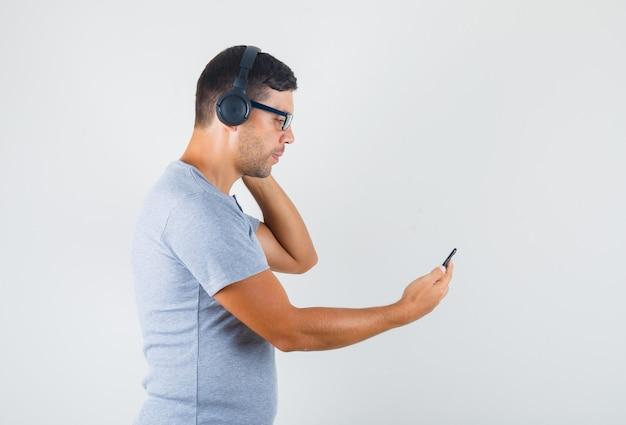 Młody człowiek w szarej koszulce, okularach, słuchawkach podejmowania wideokonferencji