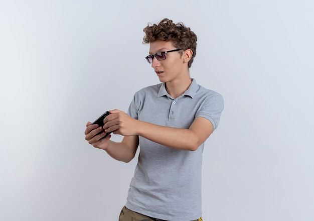 Młody człowiek w szarej koszulce polo, patrząc na ekran swojego smartfona, grając w gry stojąc na białej ścianie