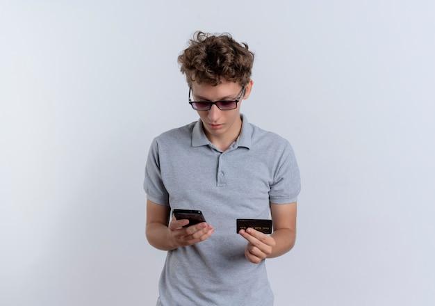 Młody człowiek w szarej koszulce polo, patrząc na ekran swojego smartfona trzymając kartę kredytową mylić stojąc na białej ścianie