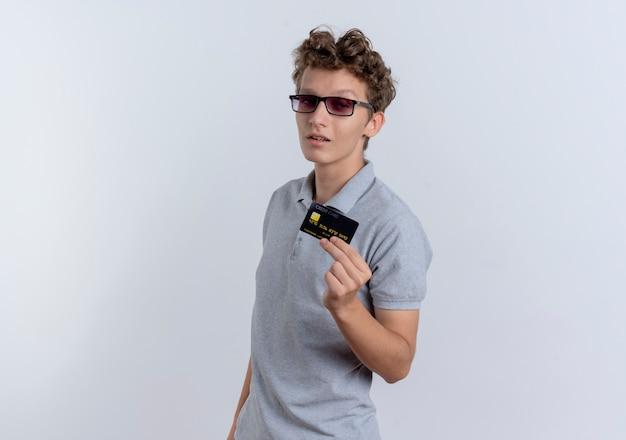 Młody człowiek w szarej koszulce polo pokazując kartę kredytową pewnie stojąc na białej ścianie