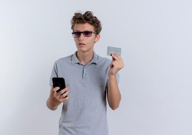 Młody człowiek w szarej koszulce polo trzymając smartfon pokazując kartę kredytową mylić stojąc na białej ścianie