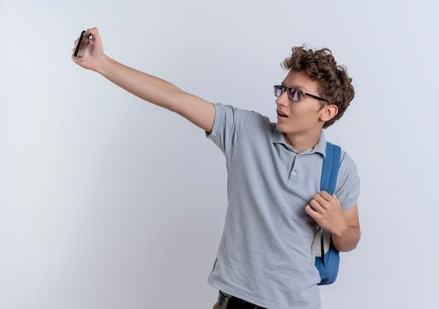 Młody człowiek w szarej koszulce polo trzymając smartfon robi selfie uśmiechnięty stojący nad białą ścianą