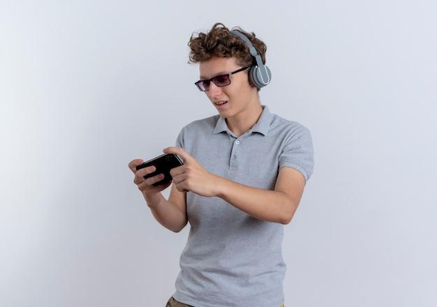 Młody człowiek w szarej koszulce polo ze słuchawkami, trzymając smartfon palying gry stojąc na białej ścianie