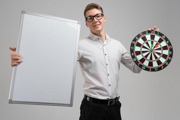Młody człowiek w szkłach z celem z strzałkami w centrum i pustą deską w jego rękach odizolowywać na bielu