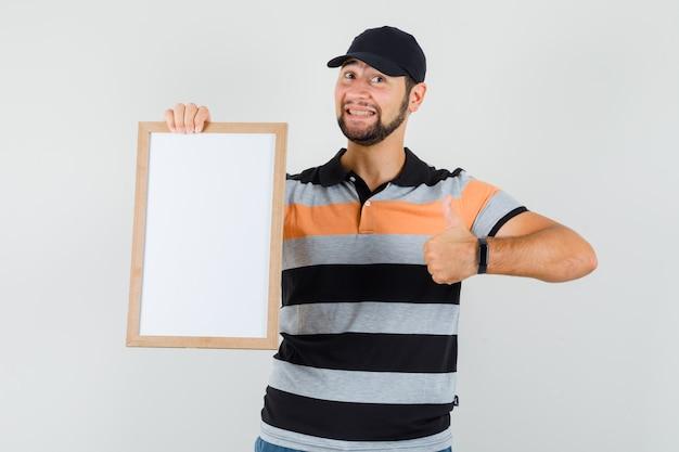 Młody człowiek w t-shirt, czapka z daszkiem, trzymając pustą ramkę, pokazując kciuk do góry i patrząc zadowolony, widok z przodu.