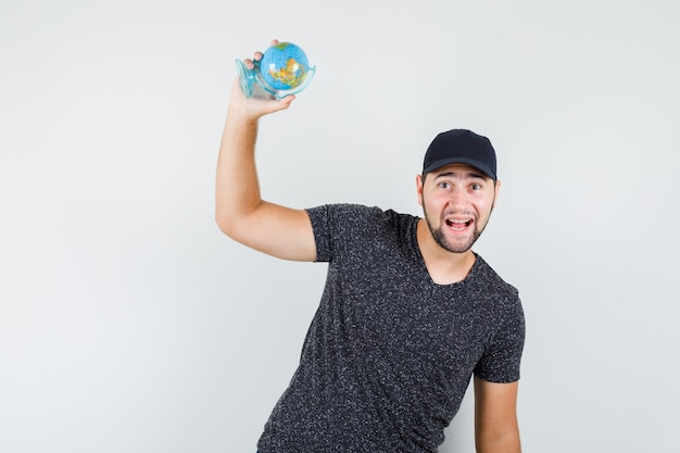 Młody człowiek w t-shirt i czapce trzymający światową kulę ziemską i wyglądający wesoło