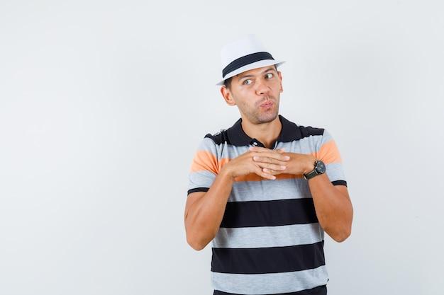 Młody człowiek w t-shirt i kapeluszu łączący palce, odwracający wzrok i wyglądający zaciekawiony
