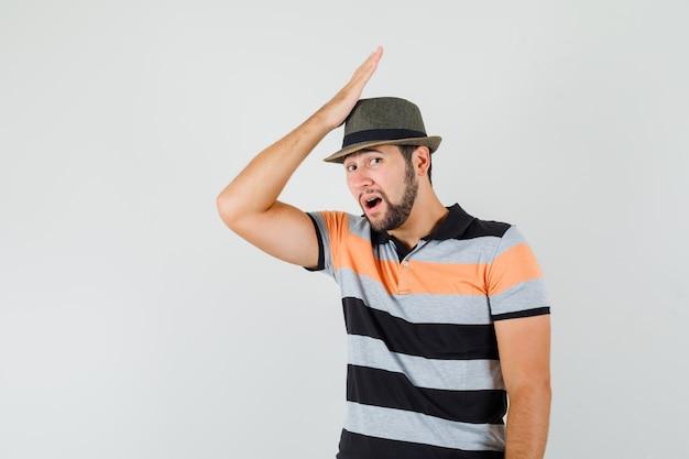 Młody człowiek w t-shirt, kapelusz dotykając czoła dłonią i patrząc żałośnie, widok z przodu.