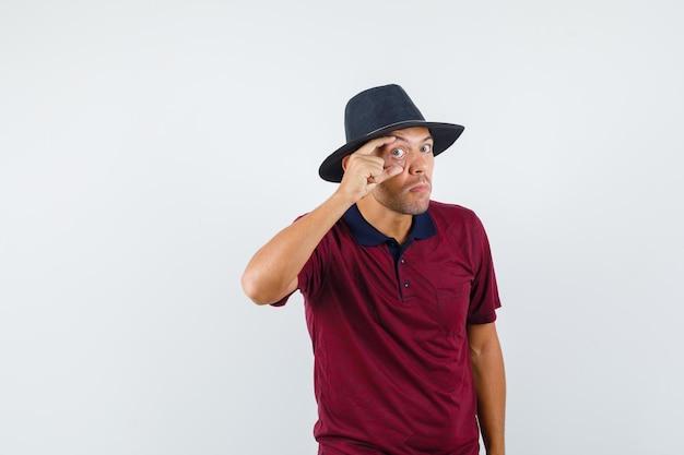 Młody człowiek w t-shirt, kapelusz otwierający oko palcami, widok z przodu.