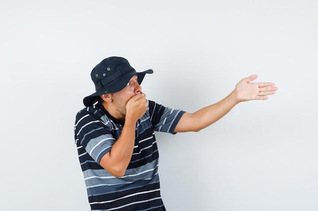 Młody człowiek w t-shirt, kapelusz, trzymając rękę na ustach i patrząc przestraszony, widok z przodu.