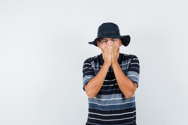 Młody człowiek w t-shirt, kapelusz, trzymając się za ręce na twarzy i patrząc przestraszony, widok z przodu.