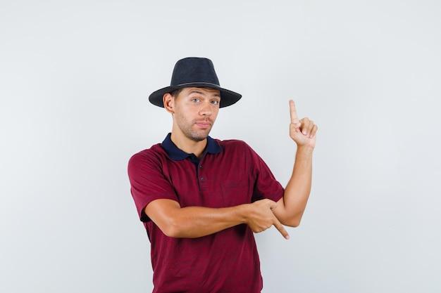Młody człowiek w t-shirt, kapelusz wskazuje w górę iw dół, widok z przodu.