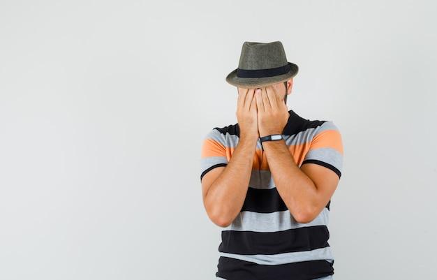 Młody człowiek w t-shirt, kapelusz zakrywający twarz rękami i wyglądający na zmartwionego, widok z przodu.