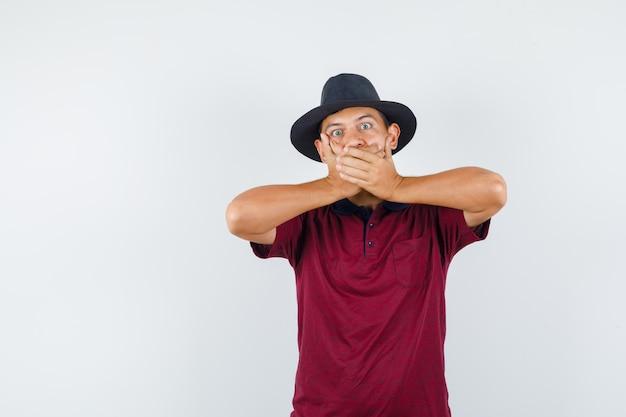 Młody człowiek w t-shirt, kapelusz zakrywający usta rękami i patrząc przestraszony, widok z przodu.
