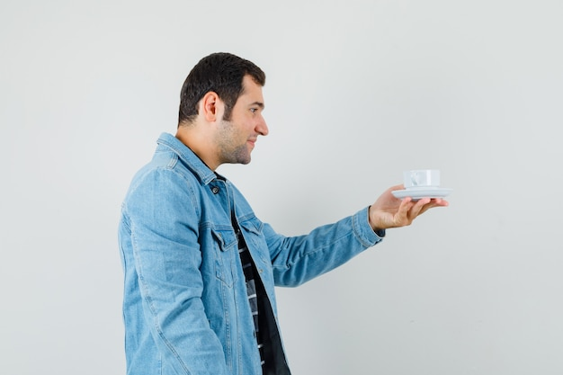 Młody człowiek w t-shirt, kurtka, patrząc na filiżankę herbaty i wyglądający wesoło.