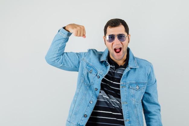 Młody człowiek w t-shirt, kurtka pokazująca mięśnie ramion i wyglądający energicznie