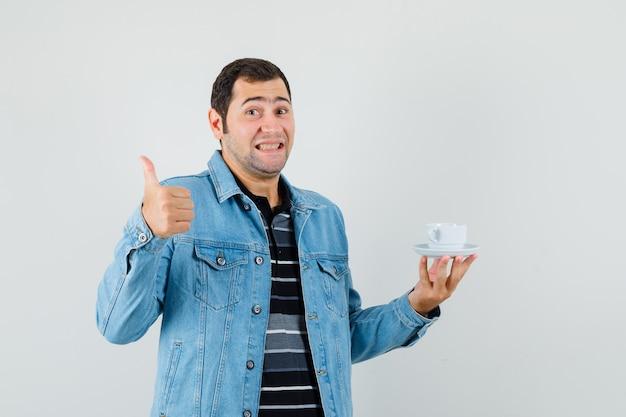 Młody człowiek w t-shirt, kurtka, trzymając filiżankę herbaty, pokazując kciuk do góry i wyglądający na szczęśliwego